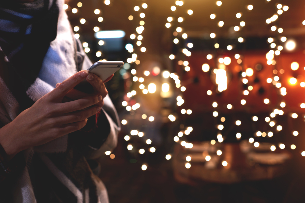 woman on phone in front of Christmas lights
