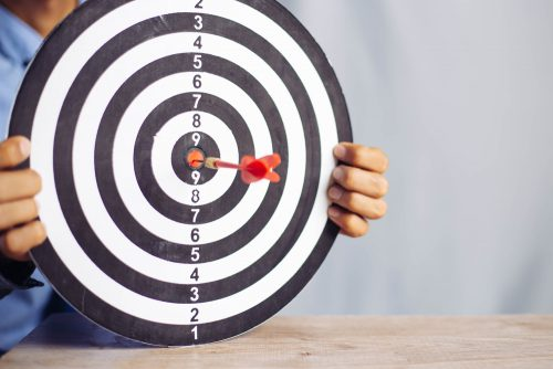 Businessman,Holding,A,Darts,Aiming,At,The,Target,Center,Business